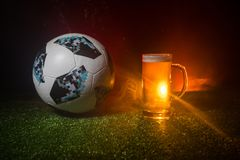 BAKU,AZERBAIJAN - JUNE 23, 2018 : Official Russia 2018 World Cup football ball The Adidas Telstar 18 and single beer glass on gree. BAKU,AZERBAIJAN - JUNE 23 royalty free stock photography