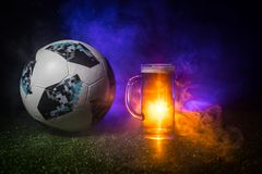 BAKU,AZERBAIJAN - JUNE 23, 2018 : Official Russia 2018 World Cup football ball The Adidas Telstar 18 and single beer glass on gree. BAKU,AZERBAIJAN - JUNE 23 royalty free stock photo