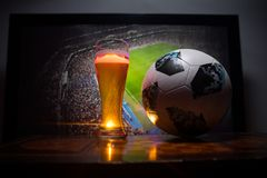 BAKU,AZERBAIJAN - JUNE 23, 2018 : Official Russia 2018 World Cup football ball The Adidas Telstar 18 and single beer glass on tabl. E at dark background with royalty free stock photos