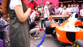BAKU, AZERBAIJAN - MAY 17, 2016: Public race car Simulator on Ferrari F1 with large audience at Expo Tuning Baku is the premier au. Tomotive specialty event in stock video footage