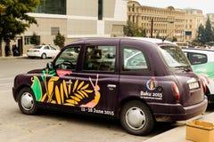 BAKU, AZERBAIJAN - OCTOBER 17, 2014: London style city taxi with 2015 first european games advertisement in Baku, Azerbaijan.  Stock Photo