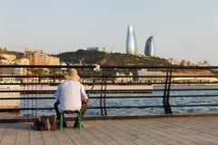 Baku, Azerbeidzjan - 16 Juli, 2015: Vissers op het Kaspische Overzees tegen de achtergrond van de stad van Baku stock fotografie