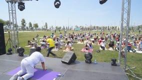 Baku, Azerbeidzjan, kan 15, 2017: Mannen en vrouwenyogaklassen tijdens de festivaldag van yoga stock videobeelden