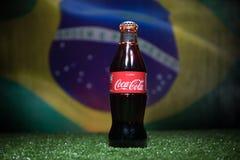 BAKU AZERBEJDŻAN, LIPIEC, - 01, 2018: Kreatywnie pojęcie koka-kola klasyk w szklanej butelce na trawie Wspiera twój kraju w Świat Fotografia Stock