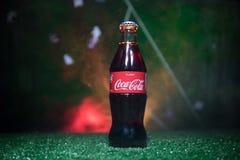 BAKU AZERBEJDŻAN, LIPIEC, - 01, 2018: Kreatywnie pojęcie koka-kola klasyk w szklanej butelce na trawie Wspiera twój kraju w Świat Zdjęcia Stock