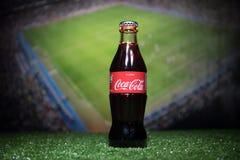 BAKU AZERBEJDŻAN, LIPIEC, - 01, 2018: Kreatywnie pojęcie koka-kola klasyk w szklanej butelce na trawie Wspiera twój kraju w Świat Obraz Royalty Free