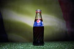 BAKU AZERBEJDŻAN, LIPIEC, - 01, 2018: Kreatywnie pojęcie Pepsi klasyk w szklanej butelce na trawie Wspiera twój kraju w pucharze  Obrazy Stock