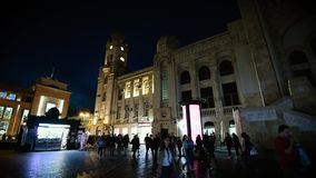 Baku Central Railway Station at night with people time lapse. Baku, Azerbaijan - Circa 2019: Cinematic wide angle view of people walking near old building of stock video