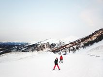 BAKURIANI, GEORGIA - 14-ОЕ ЯНВАРЯ 2018: Snowboarders na górze горы перед покатым на -piste на холодном дне солнца Стоковое фото RF