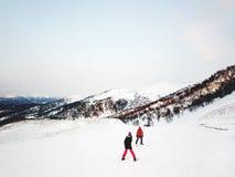 BAKURIANI, GEORGIA - 14 DE ENERO DE 2018: Snowboarders encima de la montaña antes cuesta abajo en fuera de pista en el día frío d Foto de archivo libre de regalías