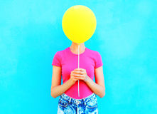 Balão de ar amarelo escondendo da cara da mulher olorful do ¡ de Ð que tem o divertimento sobre o azul imagens de stock royalty free