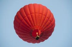 Balão de ar encarnado em um céu azul claro imagens de stock royalty free