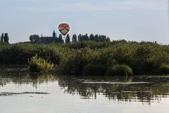 Balão de ar quente colorido no céu sobre a vegetação perto da torre de igreja italiana Foto de Stock