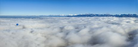 Balão de ar quente em cima das nuvens que veem montanhas dos cumes Fotos de Stock