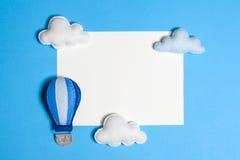 Balão de ar quente no céu azul com nuvens, quadro, copyspace Brinquedos feitos à mão de feltro Imagens de Stock