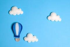 Balão de ar quente no céu azul com nuvens, quadro, copyspace Brinquedos feitos à mão de feltro Imagem de Stock Royalty Free