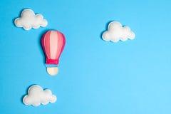 Balão de ar quente no céu azul com nuvens, quadro, copyspace Brinquedos feitos à mão de feltro Fotos de Stock