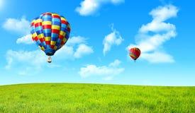 Balão de ar quente que flutua no céu sobre o campo verde Fotos de Stock