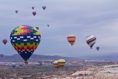 Balão de ar quente que voa sobre a paisagem da rocha em Cappadocia Turquia Fotos de Stock