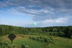 Balão de ar quente sobre o campo com céu azul Fotos de Stock Royalty Free