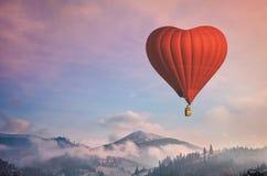 Balão de ar vermelho na forma de um voo do coração em montanhas da manhã Foto de Stock