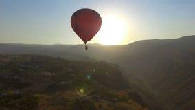 Balón de aire candente que se prepara para el aterrizaje suave en el pueblo del armenio de la montaña almacen de metraje de vídeo