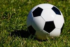 Balón de fútbol clásico en fondo de la hierba verde imagenes de archivo