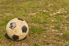 Balón de fútbol con el estadio verde del fondo Imágenes de archivo libres de regalías