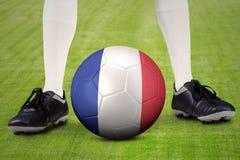 Balón de fútbol con el pie y la bandera de Francia Imagenes de archivo