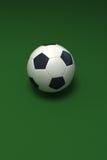 Balón de fútbol contra verde Foto de archivo