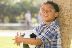 Balón de fútbol de la explotación agrícola del muchacho de la raza mezclada en el parque Imagenes de archivo