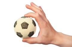 Balón de fútbol del asimiento de la mano Imagenes de archivo