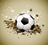 Balón de fútbol del balompié de Grunge que cae en la tierra Imagen de archivo