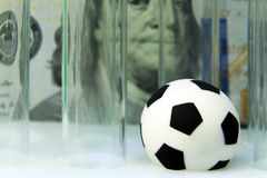 Balón de fútbol del recuerdo con los tubos de examen médico contra la perspectiva de cientos billetes de dólar Dinero y deportes, imagen de archivo