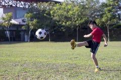 Balón de fútbol del retroceso del niño joven en campo de hierba verde Foto de archivo