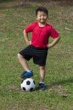 Balón de fútbol del retroceso del niño joven en campo de hierba verde Foto de archivo libre de regalías