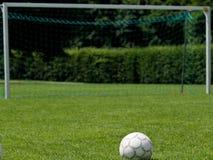 Balón de fútbol delante de la meta Imagenes de archivo
