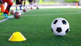 Balón de fútbol en césped artificial verde entre el fabricante de los conos con el entrenamiento borroso del equipo de fútbol almacen de video