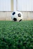 Balón de fútbol en campo Imagenes de archivo
