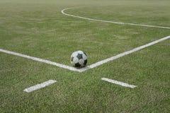 Balón de fútbol en campo de deportes en la línea fronteriza imagen de archivo