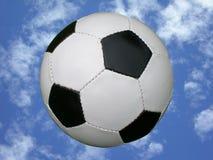 Balón de fútbol en cielo azul Fotos de archivo libres de regalías