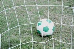 Balón de fútbol en el césped detrás de la red Imagenes de archivo