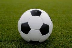 Balón de fútbol en el césped verde cerca de la puerta de la puerta Imagen de archivo libre de regalías