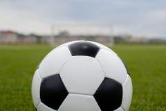 Balón de fútbol en el césped verde cerca de la puerta de la puerta Imagenes de archivo