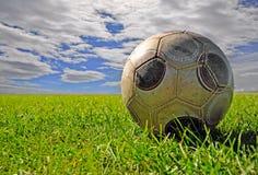 Balón de fútbol en el campo contra cloudscape Fotos de archivo libres de regalías