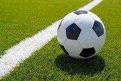 Balón de fútbol en el campo verde Imágenes de archivo libres de regalías