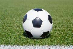 Balón de fútbol en el campo verde Fotos de archivo
