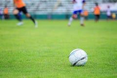 Balón de fútbol en el campo y la falta de definición del jugador en estadio Foto de archivo libre de regalías
