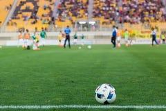 Balón de fútbol en el primero plano y los jugadores borrosos Fotos de archivo