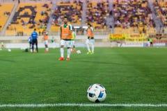 Balón de fútbol en el primero plano y los jugadores borrosos Imagenes de archivo